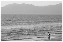 Woman holding children on the beach at sunset, Nuevo Vallarta, Nayarit. Jalisco, Mexico (black and white)