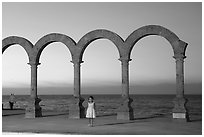 Girl standing by the Malecon arches at sunset, Puerto Vallarta, Jalisco. Jalisco, Mexico (black and white)