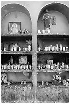Candles, flowers, and religious offerings in a roadside chapel. Mexico ( black and white)