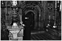 Christian Orthodox priest lighting candles. Jerusalem, Israel (black and white)
