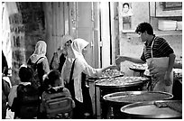 Muslem women purchasing sweets. Jerusalem, Israel (black and white)