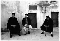 Copt monks and pilgrim in the Ethiopian Monastery. Jerusalem, Israel (black and white)