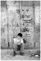 Young boy sitting in front of a closed store, Hebron. West Bank, Occupied Territories (Israel) ( black and white)