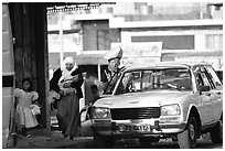 Women next to an old French Peugeot car, Hebron. West Bank, Occupied Territories (Israel) ( black and white)