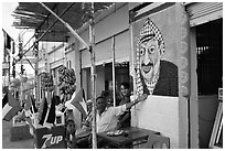 Palestinian cafe owner pointing proudly to a painting of Yasser Arafat, Jericho. West Bank, Occupied Territories (Israel) ( black and white)