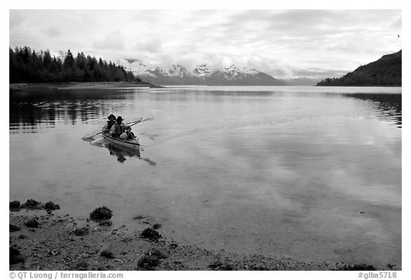 Kayakers paddle a double kayak in Hugh Miller Inlet. Glacier Bay National Park, Alaska