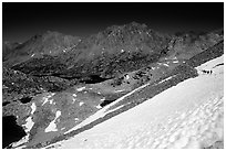 Backpackers on a snow field at a high pass. Kings Canyon National Park, California (black and white)