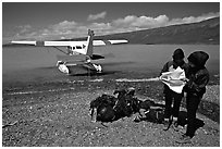 Backpackers dropped off by floatplane on Lake Turquoise orient themselves on the map. Lake Clark National Park, Alaska (black and white)