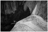 Climber near the top of Lost Arrow spire with Yosemite Falls behind. Yosemite National Park, California (black and white)