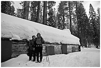 Skiing couple in front of the Mariposa Grove Museum in winter. Yosemite National Park, California (black and white)