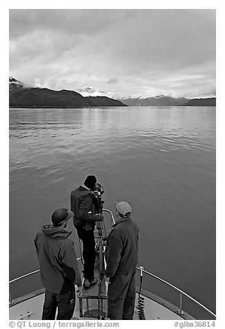 Film crew working on the bow of a small boat. Glacier Bay National Park, Alaska, USA.