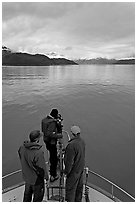 Film crew working on the bow of a small boat. Glacier Bay National Park, Alaska, USA. (black and white)