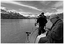 Film producer taking notes as crew films. Glacier Bay National Park, Alaska, USA. (black and white)