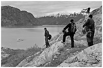 Film crew carrying a motion picture camera down rocky slopes. Glacier Bay National Park, Alaska, USA. (black and white)