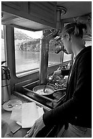 Woman cooking eggs aboard small tour boat, with glacier outside. Glacier Bay National Park, Alaska, USA. (black and white)