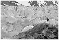 Hiker on a hill below Reid Glacier. Glacier Bay National Park, Alaska, USA. (black and white)