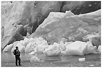 Hiker looking at ice wall at the front of Reid Glacier. Glacier Bay National Park, Alaska, USA. (black and white)