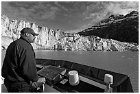 Captain guiding boat near Lamplugh glacier. Glacier Bay National Park, Alaska, USA. (black and white)