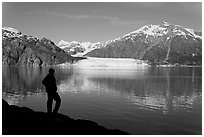 Man in silhouette looking at Tarr Inlet, Fairweather range and Margerie Glacier. Glacier Bay National Park, Alaska, USA. (black and white)