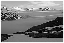 Low clouds, partly melted snow cover, and mountains. Kenai Fjords National Park, Alaska, USA. (black and white)