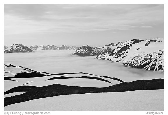 Dark bands of freshly uncovered terrain, snow, and low clouds, dusk. Kenai Fjords National Park (black and white)