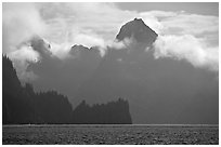 Peak emerging from the fog above bay waters. Kenai Fjords National Park, Alaska, USA. (black and white)
