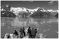 People looking at glaciers as boat crosses ice-chocked waters, Northwestern Fjord. Kenai Fjords National Park, Alaska, USA. (black and white)