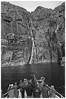 Passengers looking at waterfalls from  bow of tour boat, Cataract Cove. Kenai Fjords National Park, Alaska, USA. (black and white)