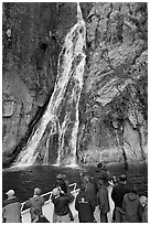 Passengers look at waterfall from tour boat, Cataract Cove, Northwestern Fjord. Kenai Fjords National Park, Alaska, USA. (black and white)
