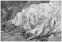 Family hiking on moraine at the base of Exit Glacier. Kenai Fjords National Park, Alaska, USA. (black and white)