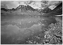 Shore of Turqouise Lake with Telaquana Mountains reflected in silty water. Lake Clark National Park, Alaska, USA. (black and white)