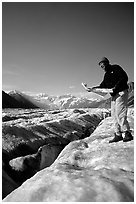 Hiker checks map on Root Glacier. Wrangell-St Elias National Park, Alaska, USA. (black and white)