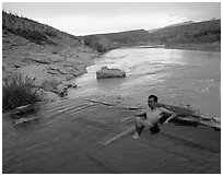 Visitor relaxes in hot springs next to Rio Grande. Big Bend National Park, Texas, USA. (black and white)