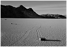 Tracks, moving stone on Racetrack playa and Ubehebe Peak, late afternoon. Death Valley National Park, California, USA. (black and white)