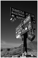 Tea kettle Junction sign, adorned with tea kettles. Death Valley National Park, California, USA. (black and white)