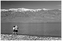 Couple watches the dragon in ephemeral lake. Death Valley National Park, California, USA. (black and white)