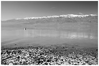 Salt formations, kayaker in a distance, and Panamint range. Death Valley National Park, California, USA. (black and white)