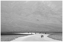 Tourists walking onto Salt Pan at Badwater. Death Valley National Park ( black and white)