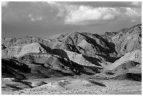 Distant Ibex Dunes at the base of multicolored mountains. Death Valley National Park ( black and white)