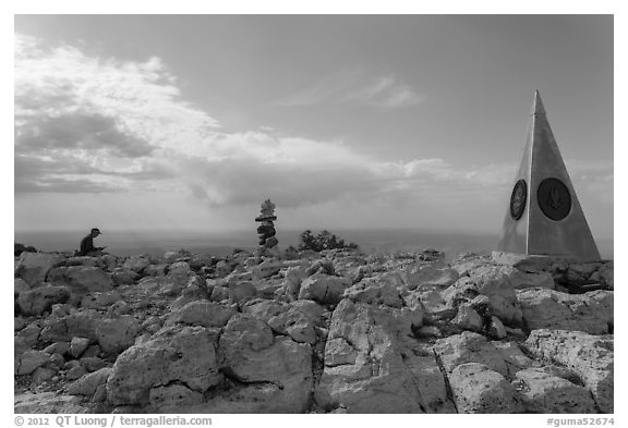 Hiker sitting on Guadalupe Peak summit with cairn and monument. Guadalupe Mountains National Park, Texas, USA.