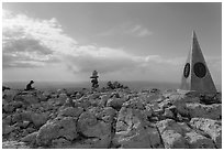 Hiker sitting on Guadalupe Peak summit with cairn and monument. Guadalupe Mountains National Park, Texas, USA. (black and white)