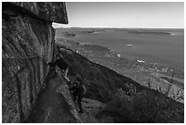Hikers on ledge with handrails, Precipice Trail. Acadia National Park ( black and white)