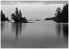 Tree-covered islet and smooth waters, Chippewa Harbor. Isle Royale National Park ( black and white)