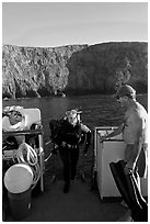 Woman diver stepping onto boat and Annacapa Island. Channel Islands National Park ( black and white)
