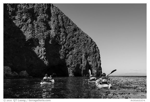 Kayakers paddling in kelp at base of sea cliff, Santa Cruz Island. Channel Islands National Park (black and white)
