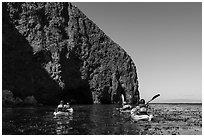 Kayakers paddling in kelp at base of sea cliff, Santa Cruz Island. Channel Islands National Park ( black and white)