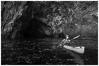 Kayaker paddling out of sea cave, Santa Cruz Island. Channel Islands National Park ( black and white)