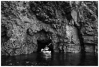 Kayaker entering narrow sea cave, Santa Cruz Island. Channel Islands National Park ( black and white)