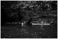 Two kayakers in sea cave with low ceiling, Santa Cruz Island. Channel Islands National Park ( black and white)