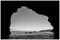 Looking out sea cave entrance with distant sea kayakers, Santa Cruz Island. Channel Islands National Park ( black and white)